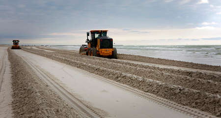 Gulf of Mexico, Padre Island, Texas. Grader adjusting send level on the beach. Beach Maintenance.