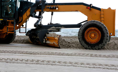 Gulf of Mexico, Padre Island, Texas. Grader adjusting send level on the beach. Beach Maintenance. Blade close up Standard-Bild - 100735428