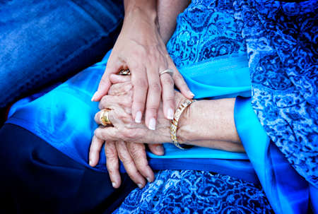 Support concept. Young hand holding wrinkled hands of Indian woman, dressed in traditional blue sari. Standard-Bild - 104816085