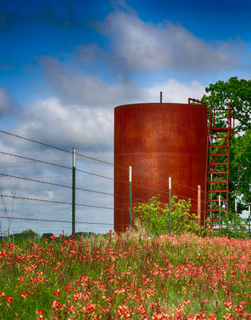 New farm barbwire fence, old rusty gas tank and field with beautiful red wild flowers. Texas rural view. Stock Photo