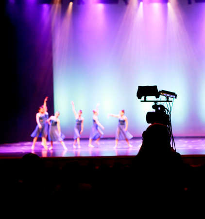 Filming dancers performance. Silhouette of camera man in front of stage with blurred dancers and colorful spotlighting.