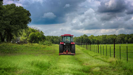 Farming: Large red tractor mowing green farmers pasture along barbwire fence Stock Photo