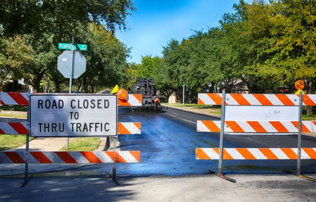 Green and quiet neighborhood street closed for maintenance.    Road closed to thru traffic sign.