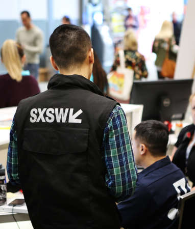 AUSTIN, TEXAS - MARCH 11, 2018: SXSW South by Southwest Annual music, film, and interactive conference and festival. Austin Convention Center, Event operation staff, SXSW sign on uniform. Standard-Bild - 121148851