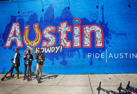 Austin, Texas, March 14, 2019, SXSW South by Southwest Annual music, film, and interactive conference and festival. Members of SXSW in front of wall painting at 6th street, using electric scooter-popular transportation in city. 新聞圖片