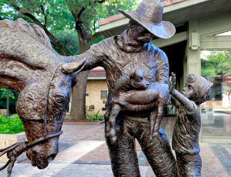 Austin, Texas, April 26, 2019.  Bronze statue of man with horses at Alumni center at University of Texas, Austin campus.