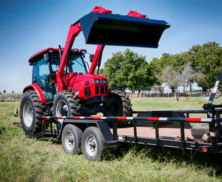 Texas farming: deliveringtowing a large red tractor.
