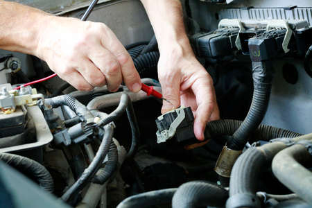 Auto technician troubleshooting electrical problems in car/truck engine
