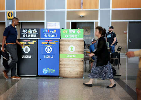 May 29, 2019. Austin–Bergstrom International Airport, Austin, Texas. Recycling bins: landfill, recycle, compost. Passenger is  taking a glass bottle to recycling bin. Focus on recycling bins.