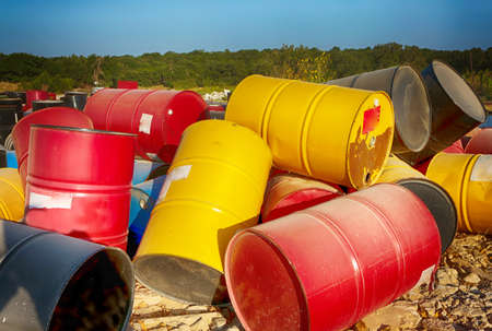 Junk yard, industrial metal recycling, colorful barrels.