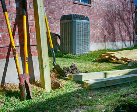 Building new fence.  Backyard with modern air conditioner, shovels and lumber for new privacy fence.