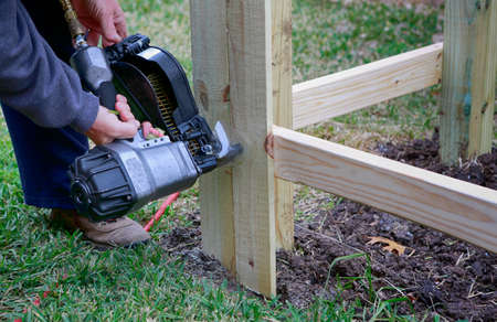 Building a new fence. Worker using a nail gun to attach wood pickets to the rail for new fence.