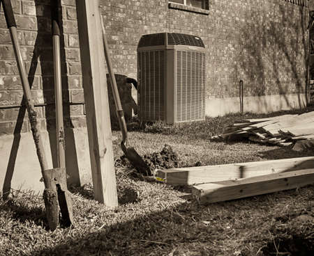 Building new fence.  Backyard with modern air conditioner, shovels and lumber for new privacy fence. Black and white.
