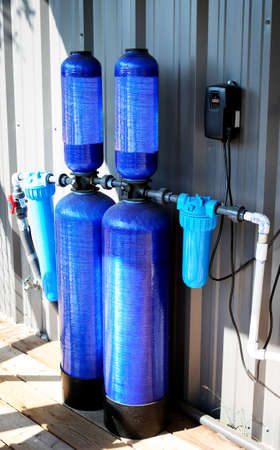 Whole house water filter - Modern reverse osmosis system outdoors on metal wall background.