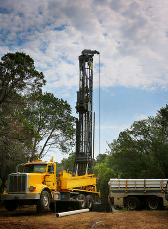 Drilling a water well on country land. Modern rotary drill rigs bore water well.