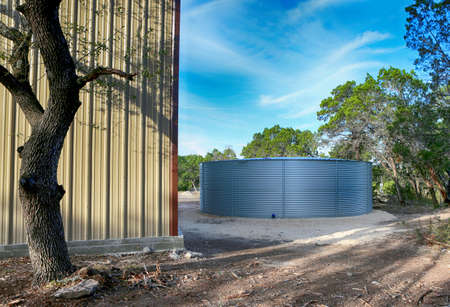 Large rain water tank, ecology friendly, in front of metallic building.