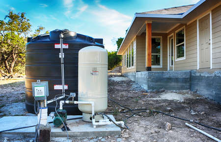 Deep water well set up in front of home construction.  Drilled draw well with pressure switch and storage tank. 免版税图像
