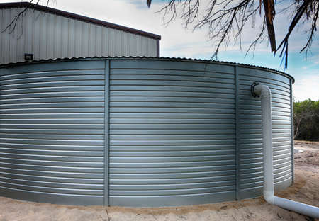 Close up of Large rain water tank, ecology friendly, in front of metallic building.