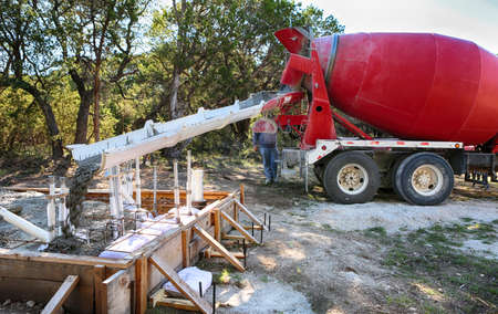 Large concrete mixing truck pouring concrete to small water house foundation Standard-Bild