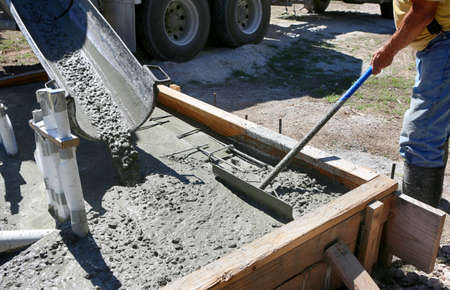 Country construction site: Concrete pouring during commercial concreting floors 免版税图像