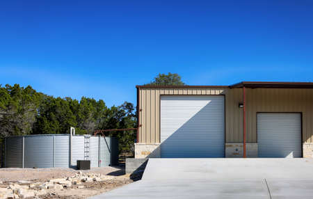 Large rain water tank, ecology friendly and large metallic building , Barn, Texas barndominium. 免版税图像