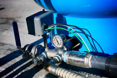 Deep water well set up. Water pressure gauge and storage tank.