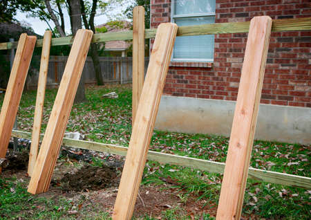 Building new privacy fence in progress: lumber set on brick house background