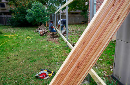 Building a new privacy fence. Carpenters working on wooded for new fence. Selective focus on lumber.