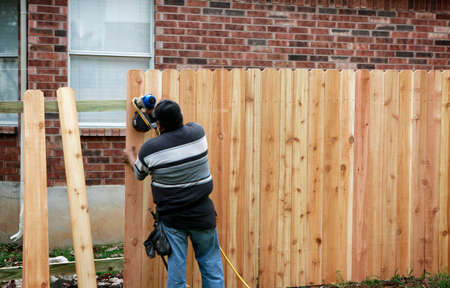 Building a new fence. Worker using a nail gun to attach wood pickets to the rail for new fence. 免版税图像 - 159060797