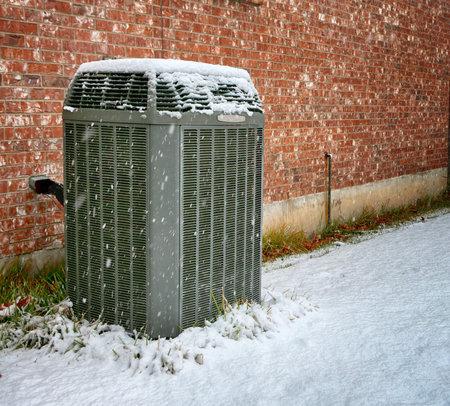 Modern high efficiency air conditioner under falling snow Standard-Bild