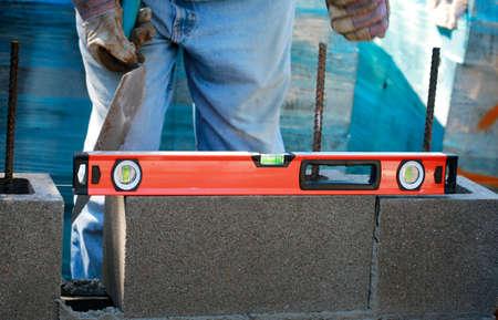 Construction site: building wall of concrete block. Mason is laying concrete blocks Standard-Bild