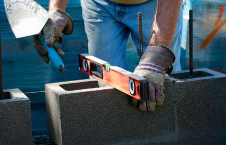 Construction site: building wall of concrete block. Mason in laying concrete blocks Standard-Bild
