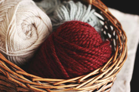 Burgundy wool yarn in wooden brown basket with needles Stock Photo