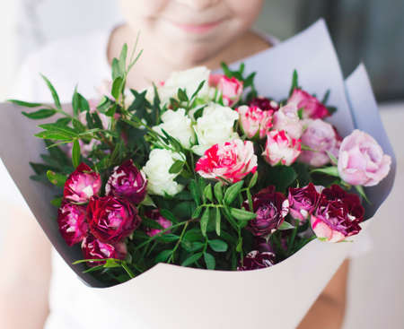 The child smiling and holding a bouquet of white and pink