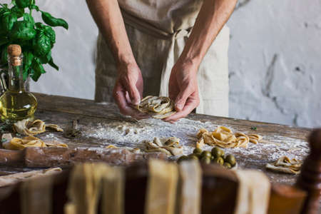 The young man preparing homemade pasta on a rustic kitchen