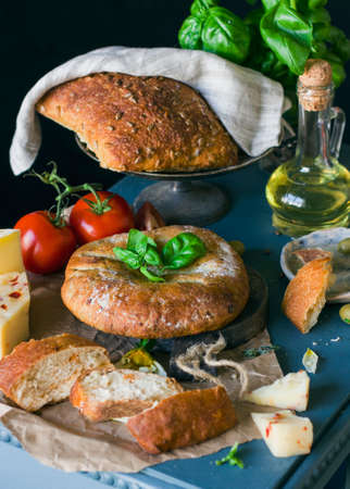 tabla de quesos: Italian Grain bread, cheese and tomatoes on blue table Foto de archivo