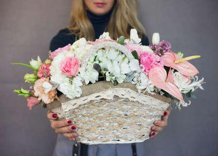 The beautiful rustic bouquet of flowers on wicker basket in woman hands