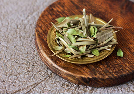 Dry olive Bay leaves in a copper plate on a wooden Board Stock Photo