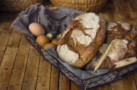 Loafs of rye bread in a basket with chicken eggs on the table Zdjęcie Seryjne