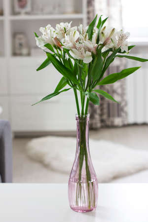 Alstroemeria flowers in narrow bottle on the table in light room at home, Scandinavian interior Stock Photo