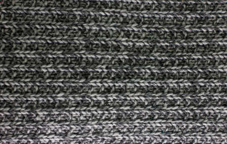 Knitted plaid blanket black grey melange texture background
