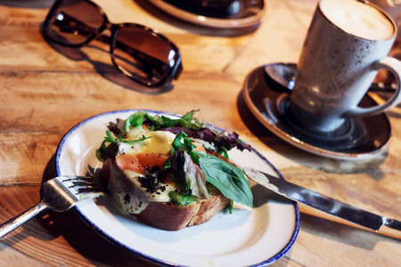 Bruschetta with poached egg and greens, cappuccino, sunglasses on the table in the cafe