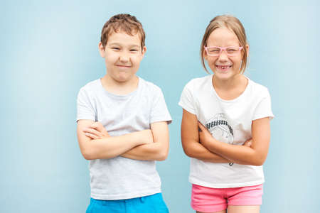 Kids brother and sister twins 8 years old standing with funny faces on blue background 스톡 콘텐츠