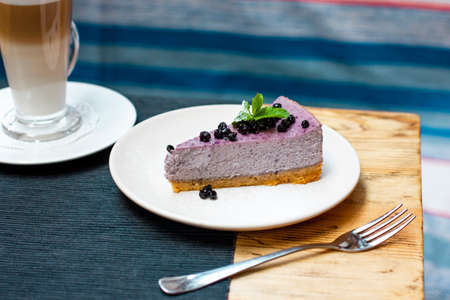 Blueberry cheesecake with berries and mint with coffee latte on the table Foto de archivo