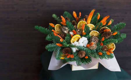 The winter composition of fir branches, dry oranges, cotton and cones, copy space