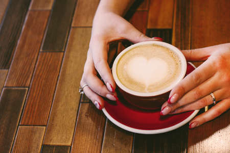 Coffee cappuccino with foam heart in woman hands with beautiful manicure on wooden background