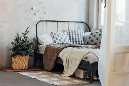 The old bed with pillows and knitted blanket. Minimalistic Christmas decor. Scandinavian interior