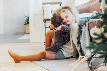 The beautiful 8 year old girl hugs toy bear and looks at the camera. New year Christmas interior
