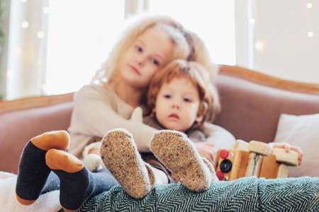 Sister hugs little brother on the couch, focus on legs in warm socks, cozy mood