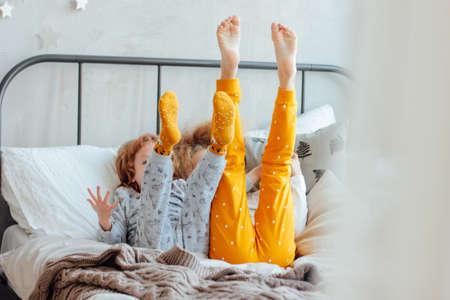 Pequeño hermano y hermana en pijama acostado en la cama, mañana acogedora, se centran en las piernas Foto de archivo
